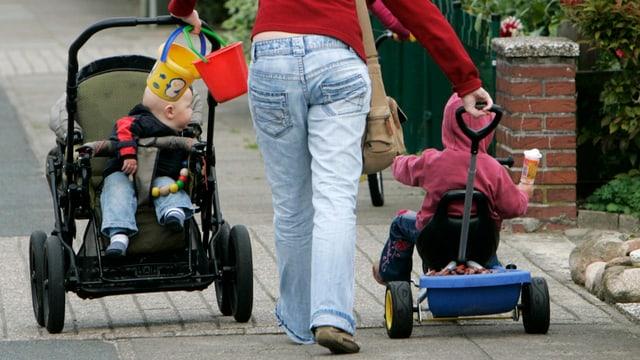 Eine Mutter stösst mit der einen Hand einen Kinderwagen mit der anderen ein Dreirad
