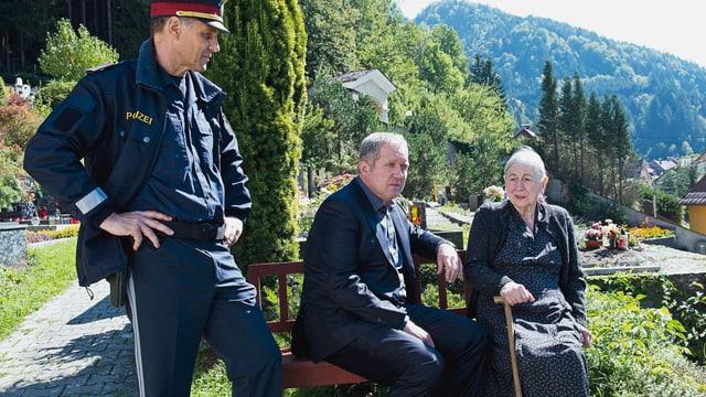 Ein Polizist und zwei Zivilisten in einer Voralpinen Landschaft.