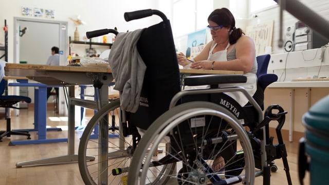 Frau an einem Tisch, daneben ein Rollstuhl