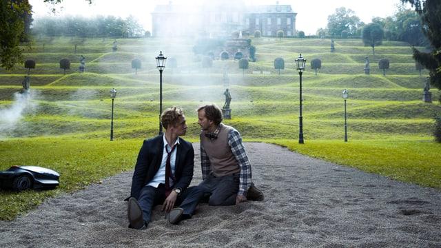 Matthias Schweighöfer und Milan Peschel sitzen auf einem Kiesweg und schauen sich  an. Schweighöfer hat in seiner Rolle als Clemens eine Drogennacht hinter sich und sieht mitgenommen aus.