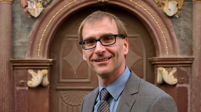 Ein lächelnder Mann mit Brille und Hemd.