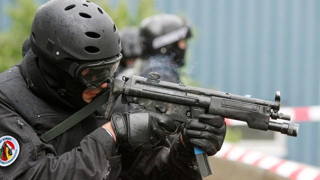 Poliszist in Kampfmontur mit Maschinenpistole im Anschlag übt einen Antiterror-Einsatz