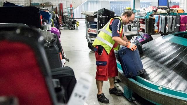 Flughafenmitarbeiter am Gepäckband