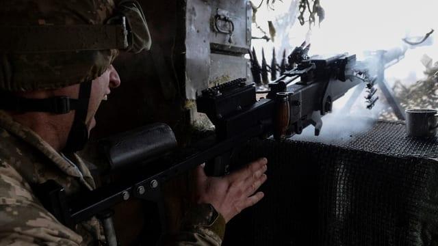 Ein ukranischer Soldat feuert mit seinem Maschinengewehr: