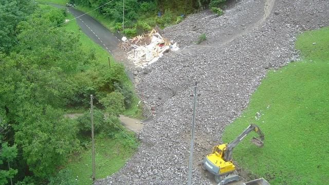 Blick auf eine von Fels und Geröll verschüttete Strasse.