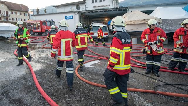 Feuerwehrleute mit langen Wasserschläuchen im Einsatz.