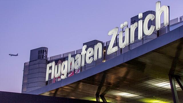 "Leuchtschrift ""Flughafen Zürich"" an Fassade, dahinter startendes Flugzeug"
