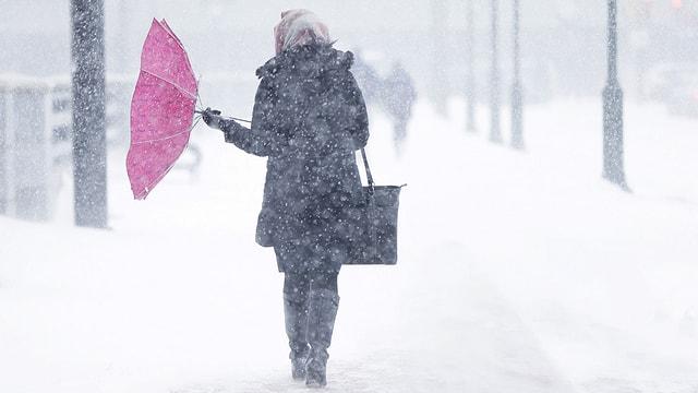 Schirm eine Frau wird von einem Schneesturm in Mitleidenschaft gezogen