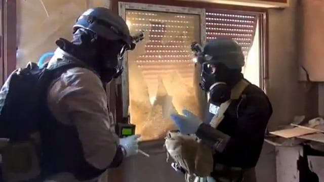 Zwei Männer in Schutzanzügen und Masken.