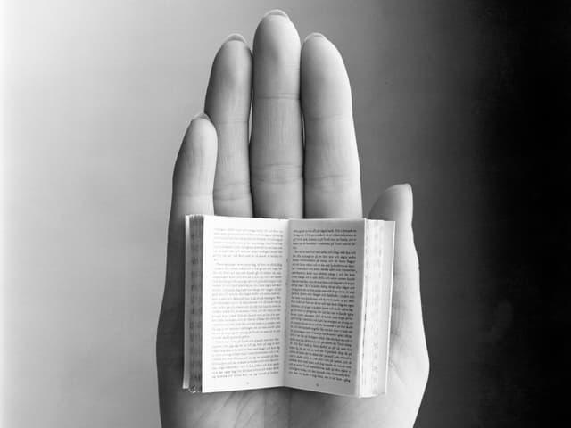 Ein sehr kleines Buch liegt offen auf der Innenseite einer Hand.