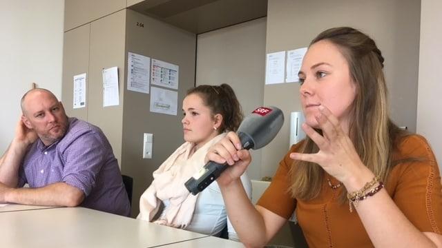Drei Teilnehmende der Podiumsdiskussion: Eine Lehrnende hält ein SRF-Mikrofon und spricht.