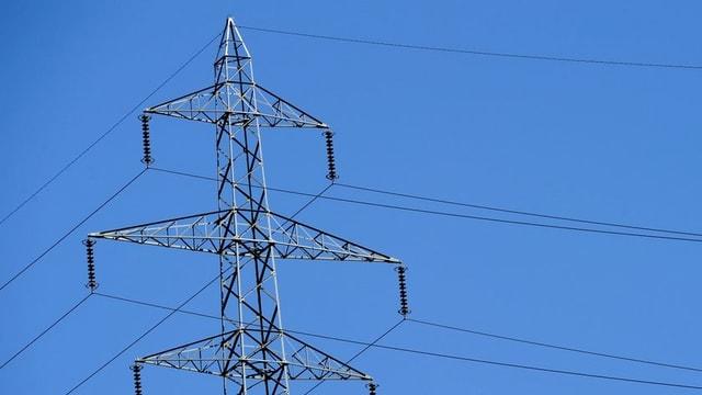 Strommast vor blauem Himmel.