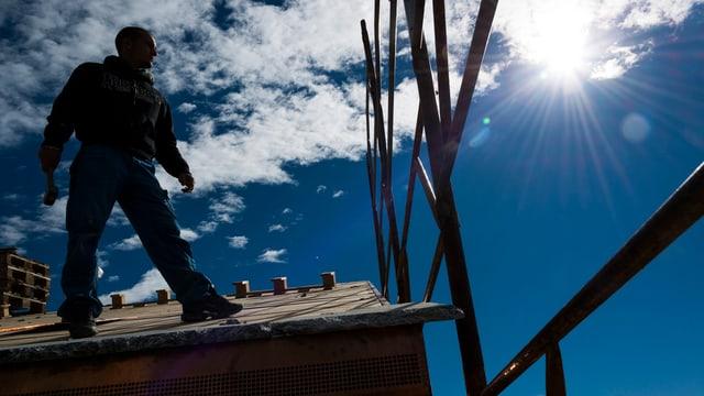 Ein Handwerker auf einem Dach.