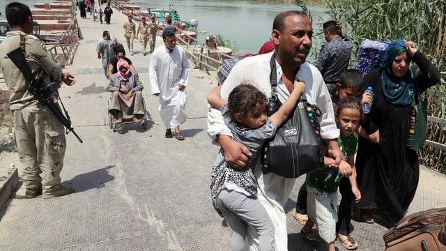 Bewohner flüchten über eine Brücke.
