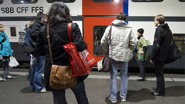 Reisende vor einem Zug der SBB.