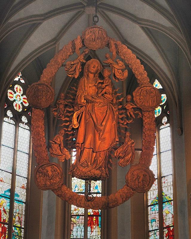 Holzskulptur, die in einem Kirchenraum hängt.