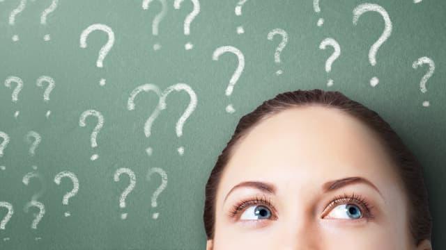 Frau blickt auf Fragezeichen über ihrem Kopf.