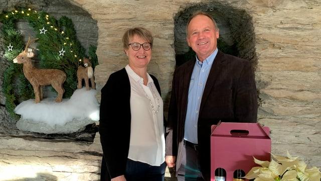 Das Winzer-Ehepaar steht im weihnächtlich geschmückten Weinkeller.