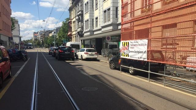 Blick auf eine Strasse mit Tramgeleisen und mehreren Autos