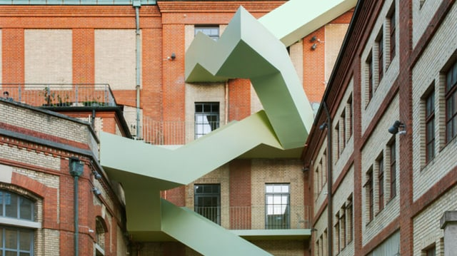 Warteck-Fassade, davor grüne Metalltreppe in Zickzackform.