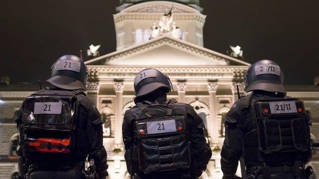 polizists en mondura e chapellinas avant chasa federala