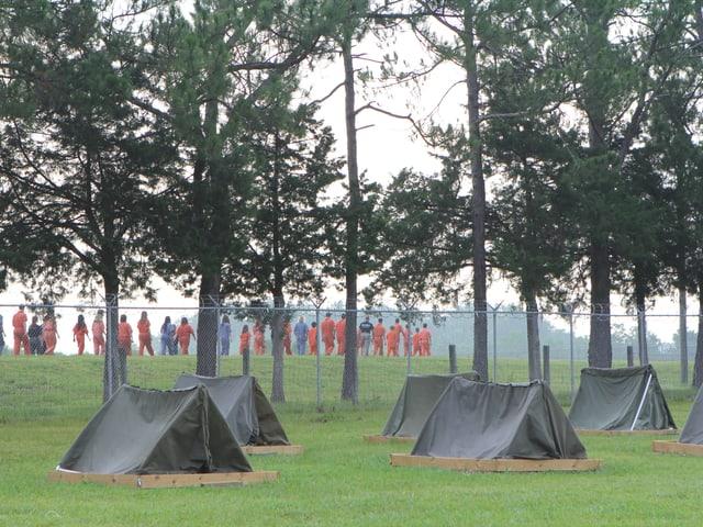 Es stehen ein paar kleine Zelte auf einer grünen Wiese. Darin schlafen die Jugendliche und Kinder.