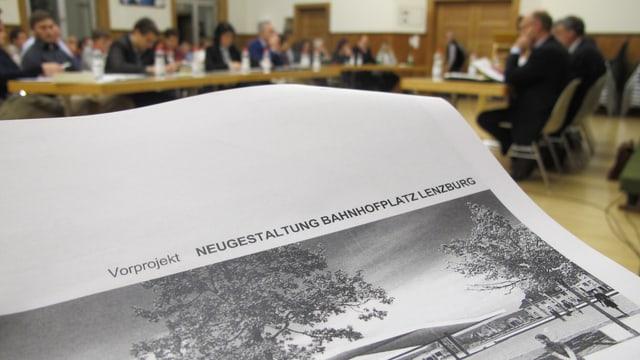 """Dossier mit dem Titel """"Vorprojekt Neugestaltung Bahnhofplatz"""" - im Hintergrund der Einwohnerrat Lenzburg."""