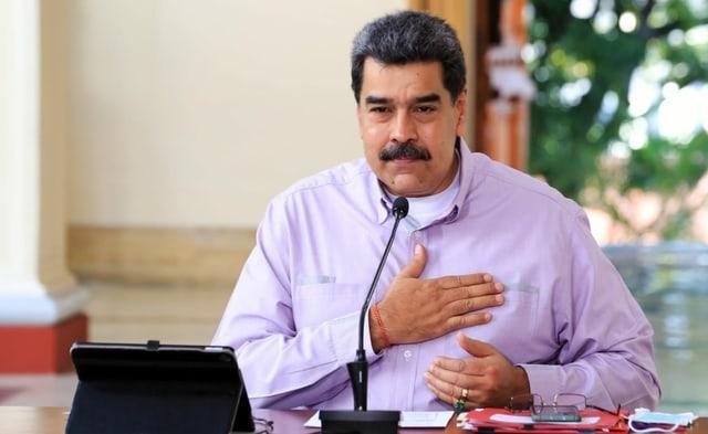 Venezuelas Präsident Nicolas Maduro fasst sich auf sein Herz.