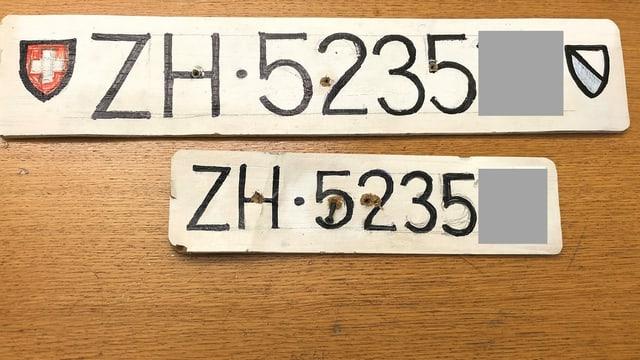 Zwei selber gemalte Autonummer liegen auf einem Holztisch.