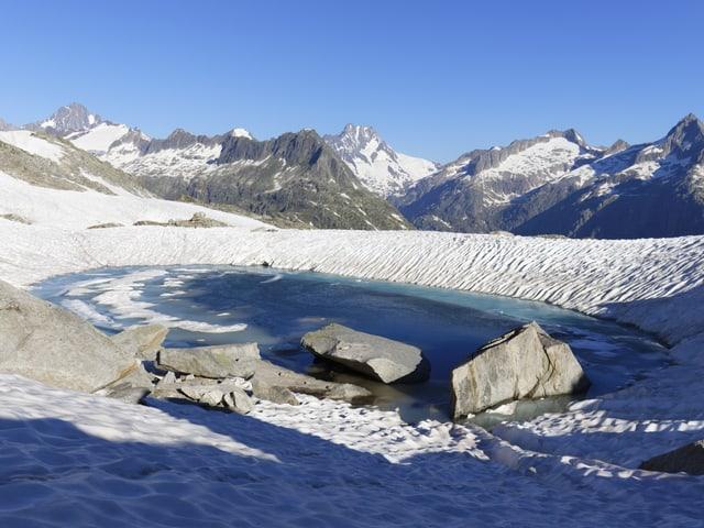 Alpine Landschaft mit Felsen, Schnee und einem kleinen Seelein.