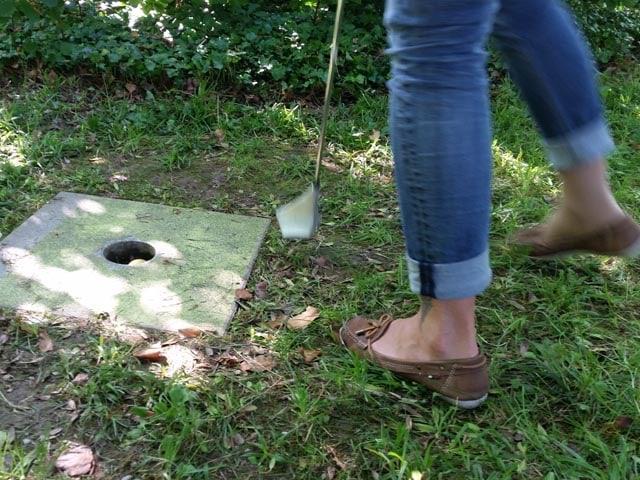 Eine Frau schiebt einen Golfball in ein dafür vorgesehenes Loch.