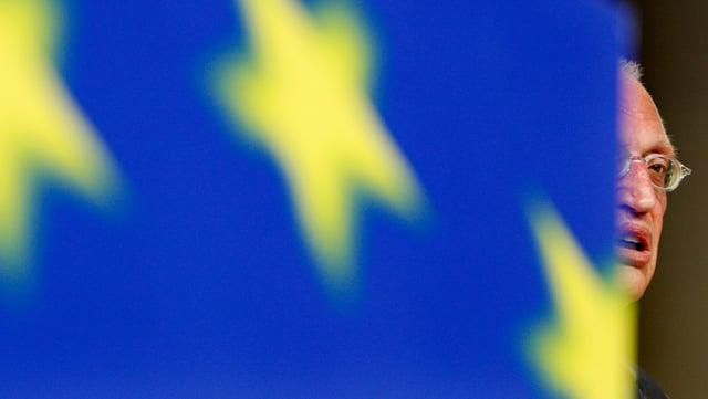 Verheugen halb versteckt hinter einer EU-Flagge.