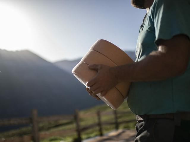 Ein Käsre trägt drei Käselaibe, im Hintergrund Bergkulisse.