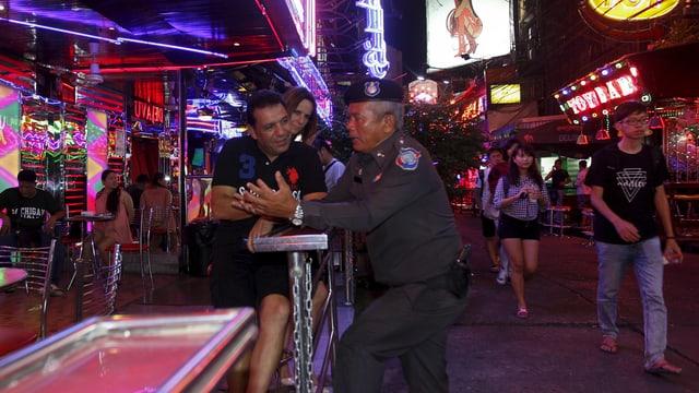 Ein thailändischer Polizist spricht mit einem Touristen