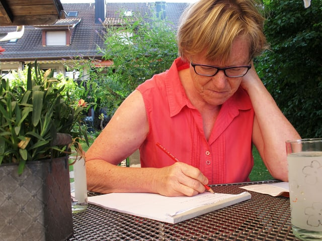 Ursula Diener sitzt am Gartentisch und schreibt.