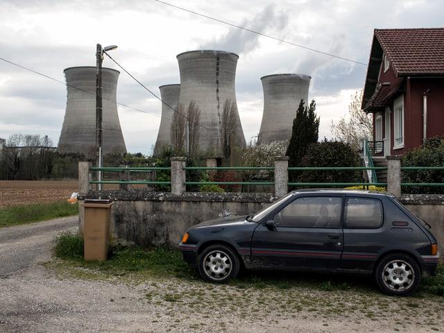 im Hintergrund vier dampfende Kühltürme, im Vordergrund ein französischer Wagen, der parkiert ist.