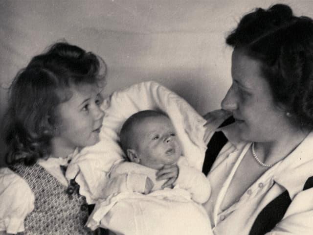 Eine Mutter hält ein Baby auf dem Arm, daneben sitzt ein kleines Mädchen.