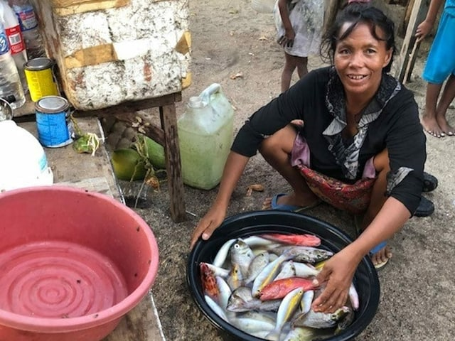 Eine Frau vor einem Kübel mit Fischen.