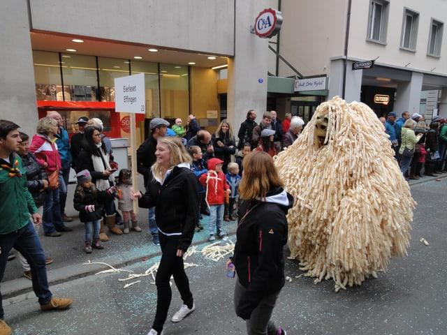 Eine Figur vollgepflastert mit Hobelspänen wandelt durch die Strassen