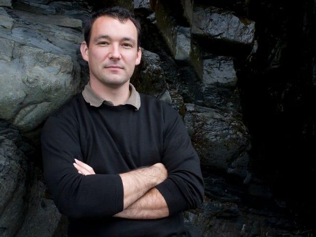 Cynan Jones steht vor einer Steinmauer.