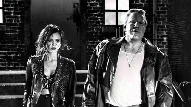 Eine Frau und ein Mann stehen vor einer Taverne. Ihnen droht etwas.