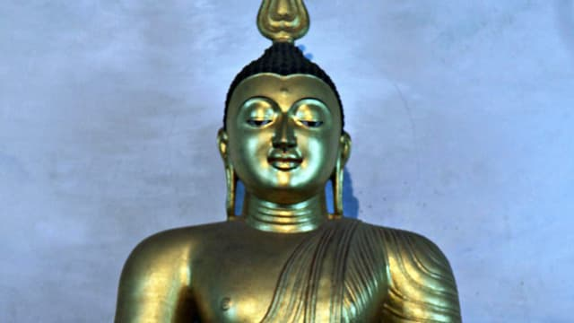 Sitzender goldener Buddha, fotografiert in Sri Lanka.