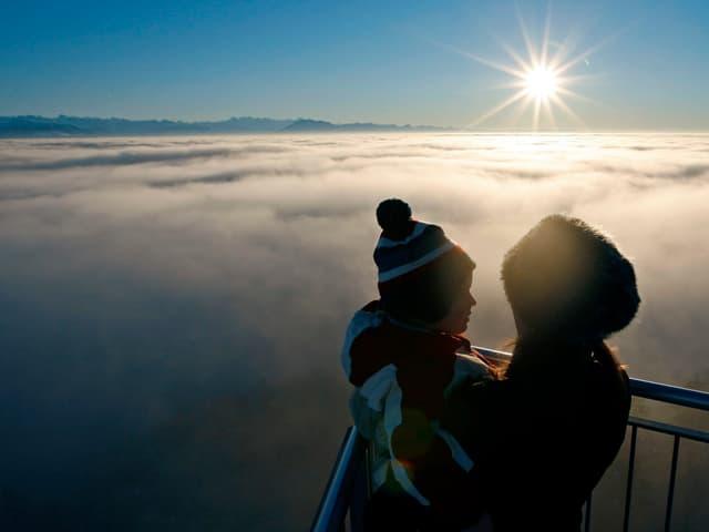 Frau mit Kind geniessen oberhalb des Hochnebels die tiefstehende Sonne.