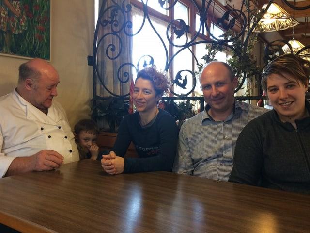 Frauen und Männer an einem Restauranttisch.