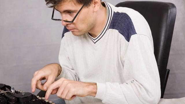 Ein Mann mit Brille sitzt an einem Pult und tippt auf einer Schreibmaschine.