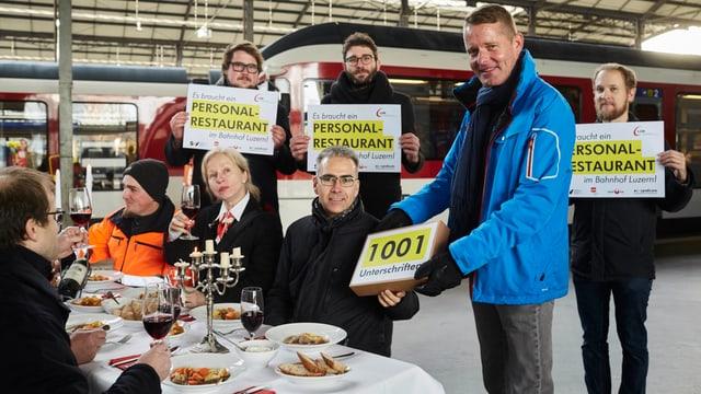 Männer und Frauen halten Schilder mit der Aufschrift «Es braucht ein Personalrestaurant» vor sich hin.