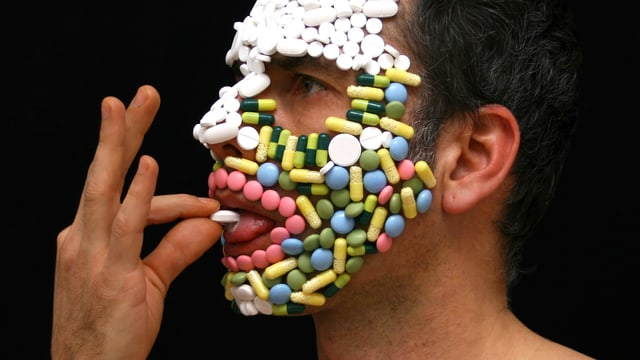 Am Gesicht eines Mannes mit nacktem Oberkörper kleben so vielle Pillen und Tabletten, dass sie zu einer Maske werden. Der Mann schluckt eine Tablette.