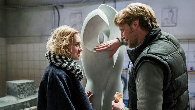 Ein Mädchen und ein Mann stehen vor einer Steinstatue und schauen sich lächelnd in die Augen.