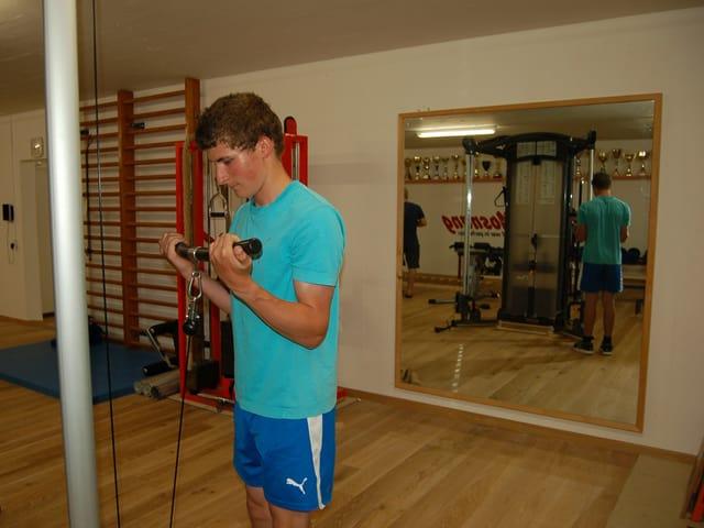 Ein junge Mann mit Hanteln in einem Raum mit verschiedenen Trainingsgeräten.