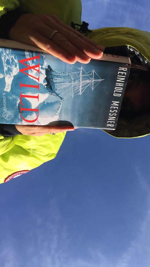 Annette König trägt eine neon-grüne Daunenjacke vor blaubem Himmel und hält «Wild» von Reinhold Messner in der Hand: